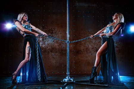 Two pole dance women standing at the pole and holding it on metallic chain. Tattoo on model body.