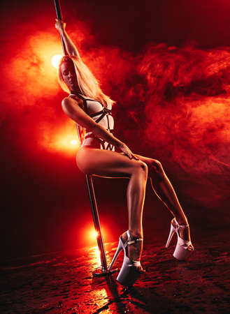Young sexy slim woman pole dancing in dark interior with red vibrant lights and smoke Stok Fotoğraf