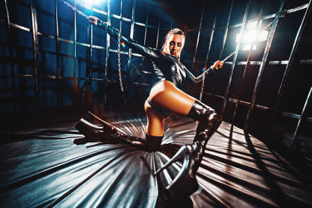 Young sexy woman in leather clothing dancing in cage with chains