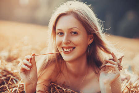 Young smiling blond woman portrait on summer field. Warm sunny light.