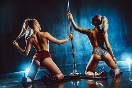 Two pole dance women standing at the pole in dark interior with blue lights.