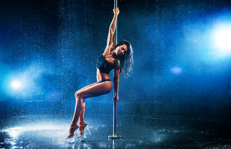 Young slim brunette woman pole dancing in dark interior with smoke and water