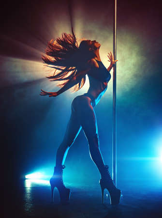 Young sexy slim brunette pole dancing woman shaking hair. Silhouette with smoke and lights. 免版税图像