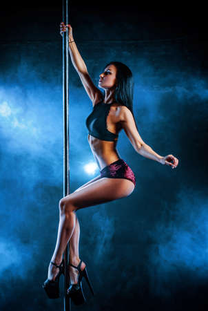 Young woman pole dancing on dark background with smoke Stock Photo