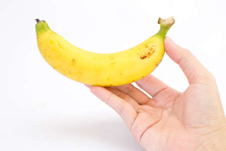 hand is holding a   banana isolated on white background Stock Photo