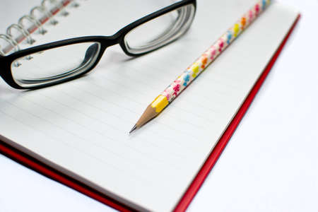 Closeup of reading glasses and pen  on the book isolated on white background photo