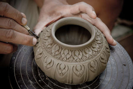 potter inflicts a decorative pattern on pot