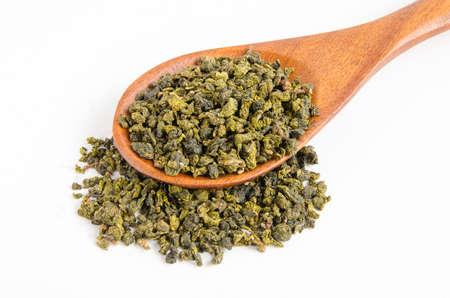 Dry-green-tea-and-wooden-shovel-on-white Stock Photo