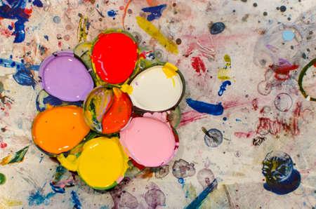 paints: Palette with paints on mix color background