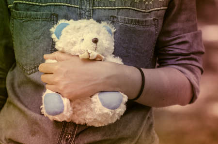 Vintage style photo of  woman with a little teddy bear toy at outdoor Stock Photo
