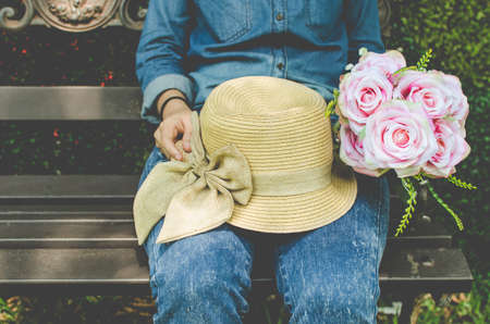Vintage style photo of  woman with hat and flowers sitting  outdoors Stock Photo