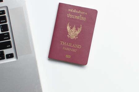 Thailand passport with laptop on white background, Find travel information