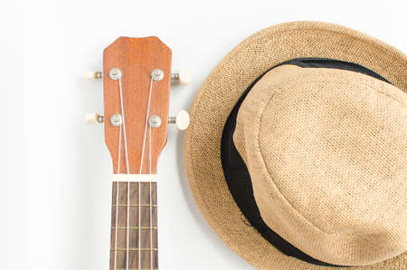 Ukulele and brown hat on white background