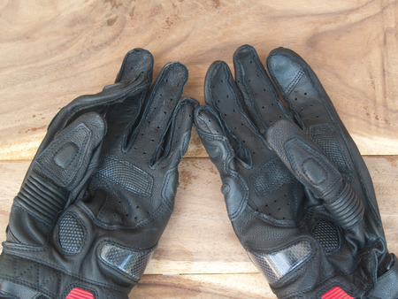 black gloves: black gloves motorcycle on old wood table,use this before ride Stock Photo
