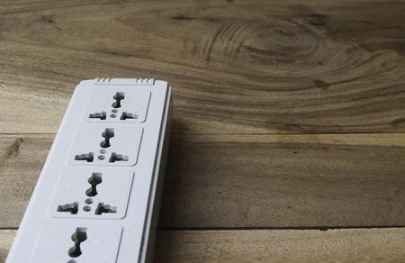 plug socket: old white plug socket on a wooden table  background Stock Photo