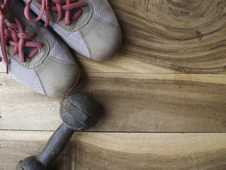 additional training: metal dumbbell and shoe on a old wooden background, for workout Stock Photo