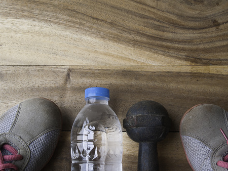 additional training: Drink water bottle ,metal dumbbell and on a old wooden background,for workout