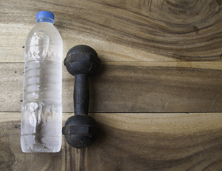 additional training: Drink water bottle and metal dumbbell on a old wooden background,plastic bottle