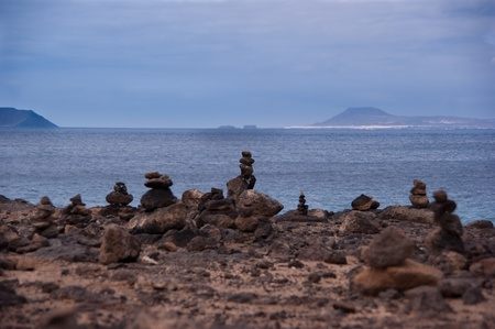 rock piles in playa blanca with fuerteventura island in the background Stock Photo - 9820672