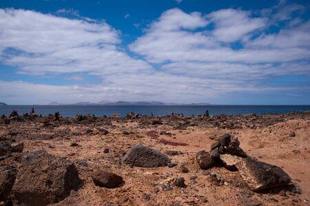 stone piles in playa blanca with fuerteventura in background Stock Photo - 9820677