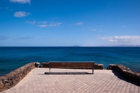 lonly empty bench in playa blanca overlooking fuerteventura
