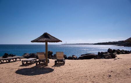 empty sunbeds in playa blanca overlooking faro de pechiguera Stock Photo - 9820674