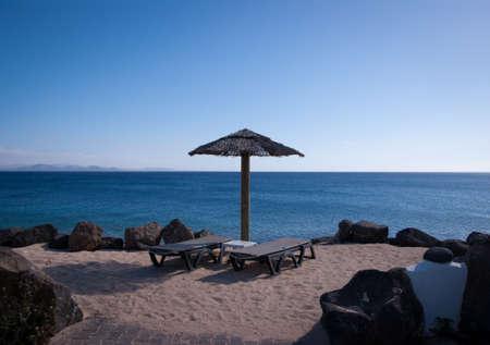 empty sunbeds in playa blanca overlooking faro de pechiguera Stock Photo