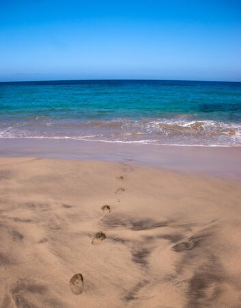 footprints leading to the ocean, playa mujeres, lanzarote Stock Photo - 9820685