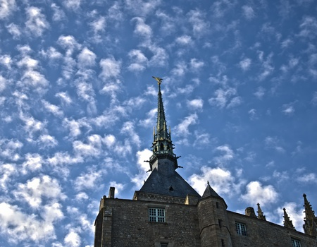 golden statue of st. michel at mont saint michel abbey on a blue sky background