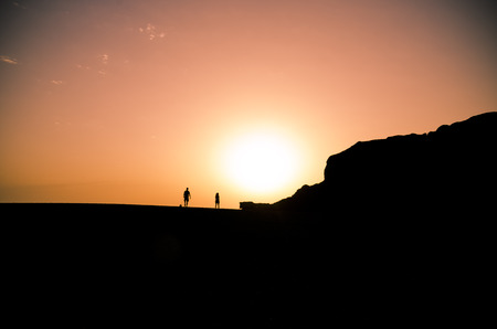 man and woman with dog walking during sunset on the beach charco de los clicos, Lanzarote, Canary Islands, Spain