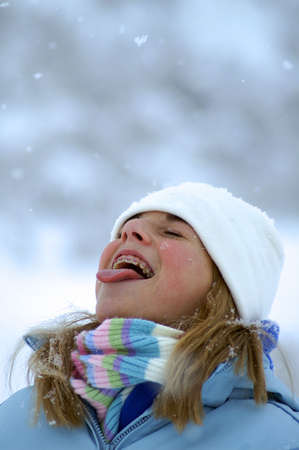 Young Girl Catching Snowflakes on her Tongue