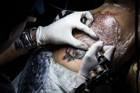 tattooer showing process of making a tattoo. Tattoo design in pattern 스톡 콘텐츠
