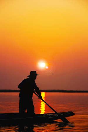 Silhouet van de mannen roeiboot, Sunset achtergrond