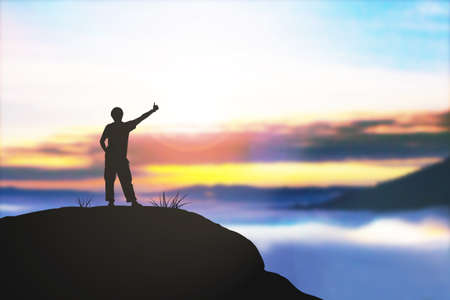 concede: Silhouette Man standing on the rocks over blurred the sunrise nature background.