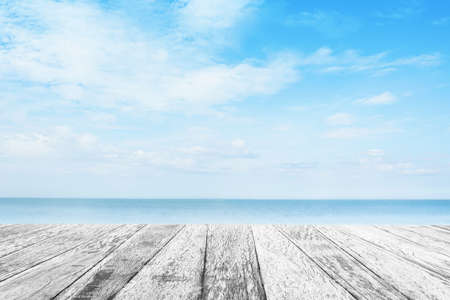 Wood tabletop foreground with sunshine clouds sky during morning background. Blue,white pastel heaven,soft focus lens flare sunlight. Abstract blurred cyan gradient of peaceful nature. Stock Photo