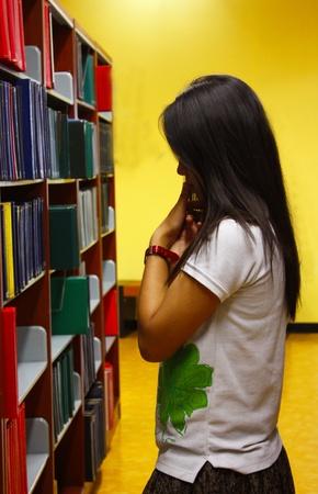 La muchacha está tomando la decisión para seleccionar el libro