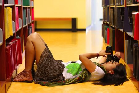 woman is shooting the camera in the library photo