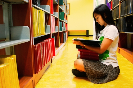 woman is reading books in the library photo