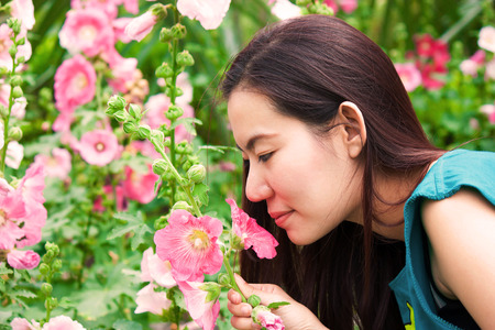gril is smellling the flower in the garden