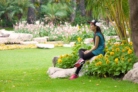 gril: girl is sitting alone among the sunflower Stock Photo