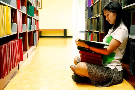 tractive: University student is reading book on the floor in the library Stock Photo