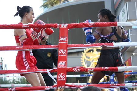 Two women Muay Thai Boxing are trying to knock each other on the ring