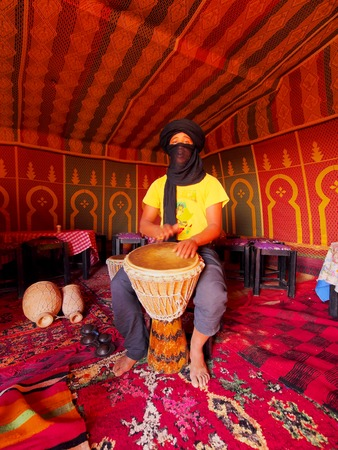 ZAGORA DESERT, MOROCCO, MAY 04: Unidentified Berber man playing the drum inside of the tent on the Zagora Desert in Morocco, May 04, 2013. Berber people live on the desert as a hundred years ago.