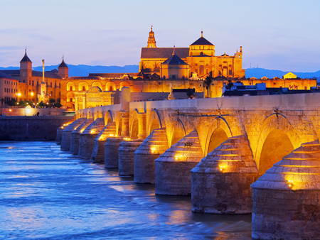 Night view of Mezquita-Catedral and Puente Romano - Mosque-Cathedral and the Roman Bridge in Cordoba, Andalusia, Spain photo