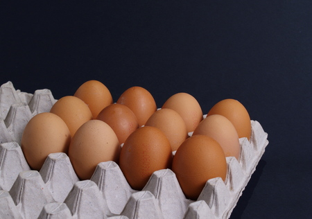 Fresh Eggs In Egg Carton On Black photo