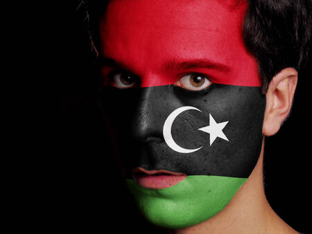 Flag of Libya Painted on a Face of a Young Man photo