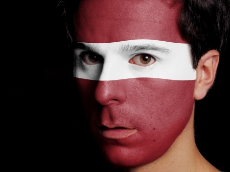 Flag of Latvia Painted on a Face of a Young Man photo