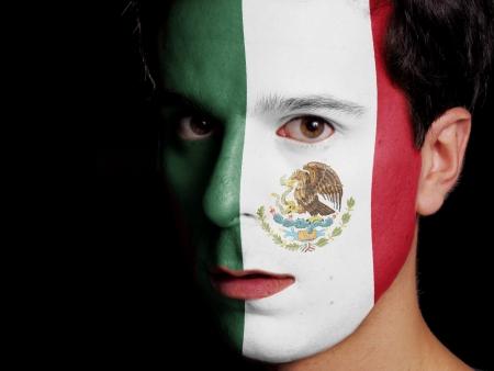 Bandera de México pintada en una cara de un hombre joven