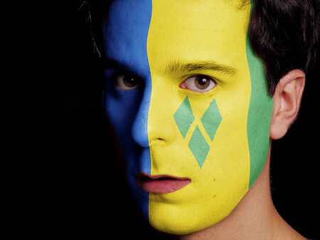 Flag of Saint Vincent and the Grenadines Painted on a Face of a Young Man photo