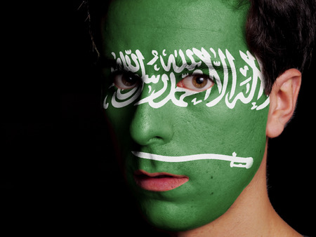 Flag of Saudi Arabia Painted on a Face of a Young Man photo